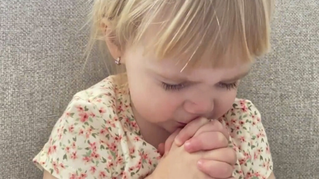 A child with hands clasped in prayer.